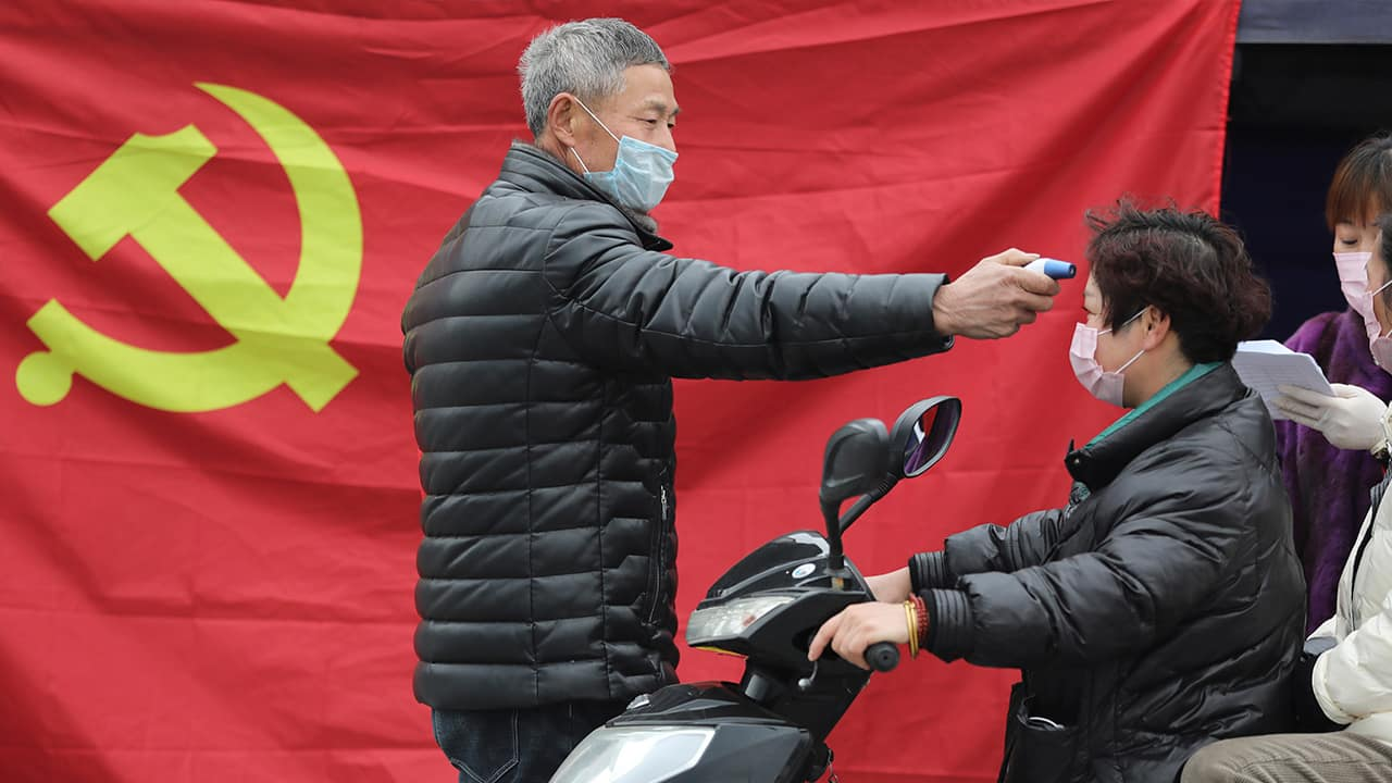 Photo of a volunteer taking the temperature of a scooter driver