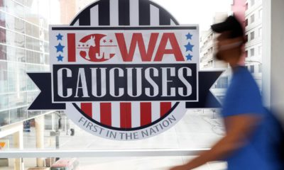 Photo of a pedestrian walking past an Iowa Caucuses sign