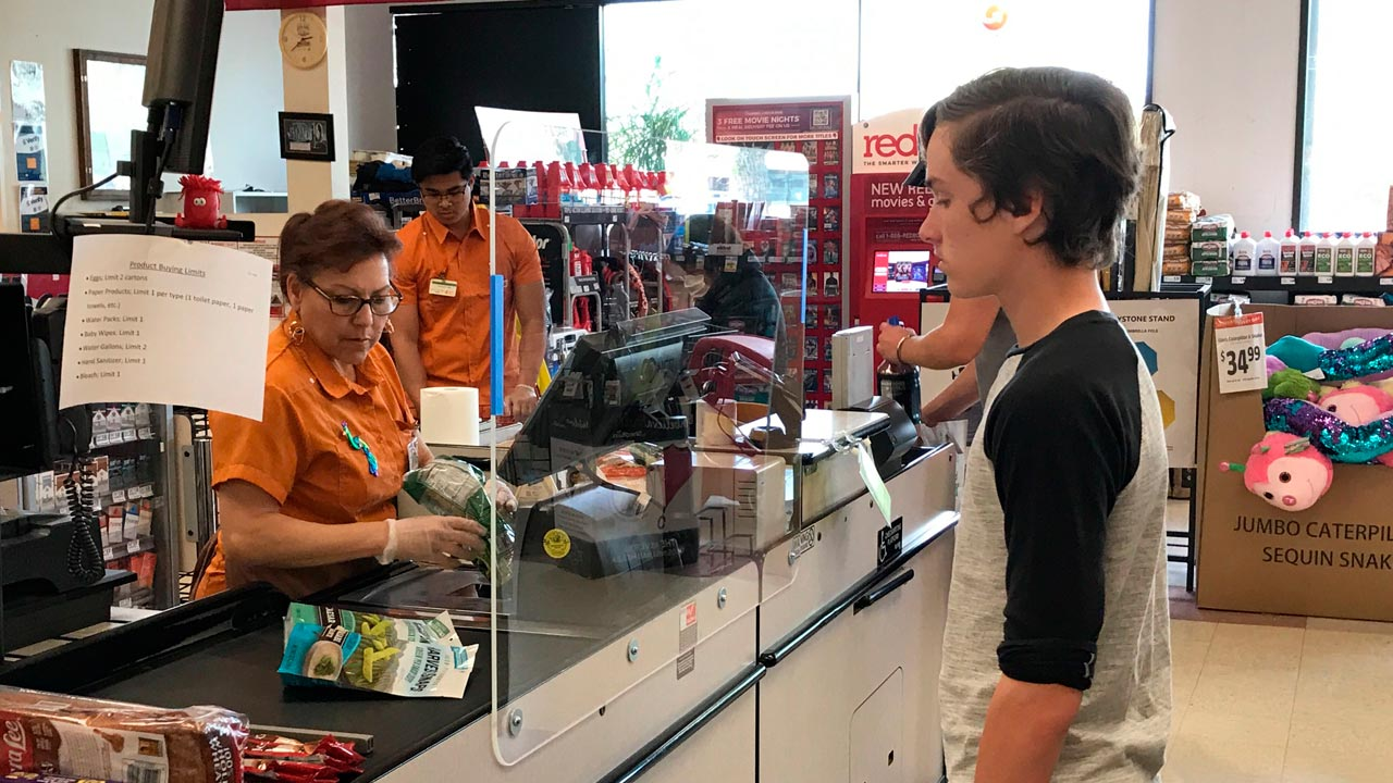 Photo of customer and grocery store cashier separated by a sneeze guard