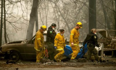 Photo of firefighters and deputies carrying a body of a Camp Fire victim
