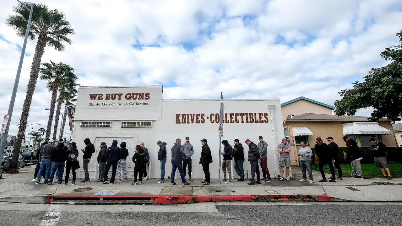 Photo of people lining up outside of a gun store