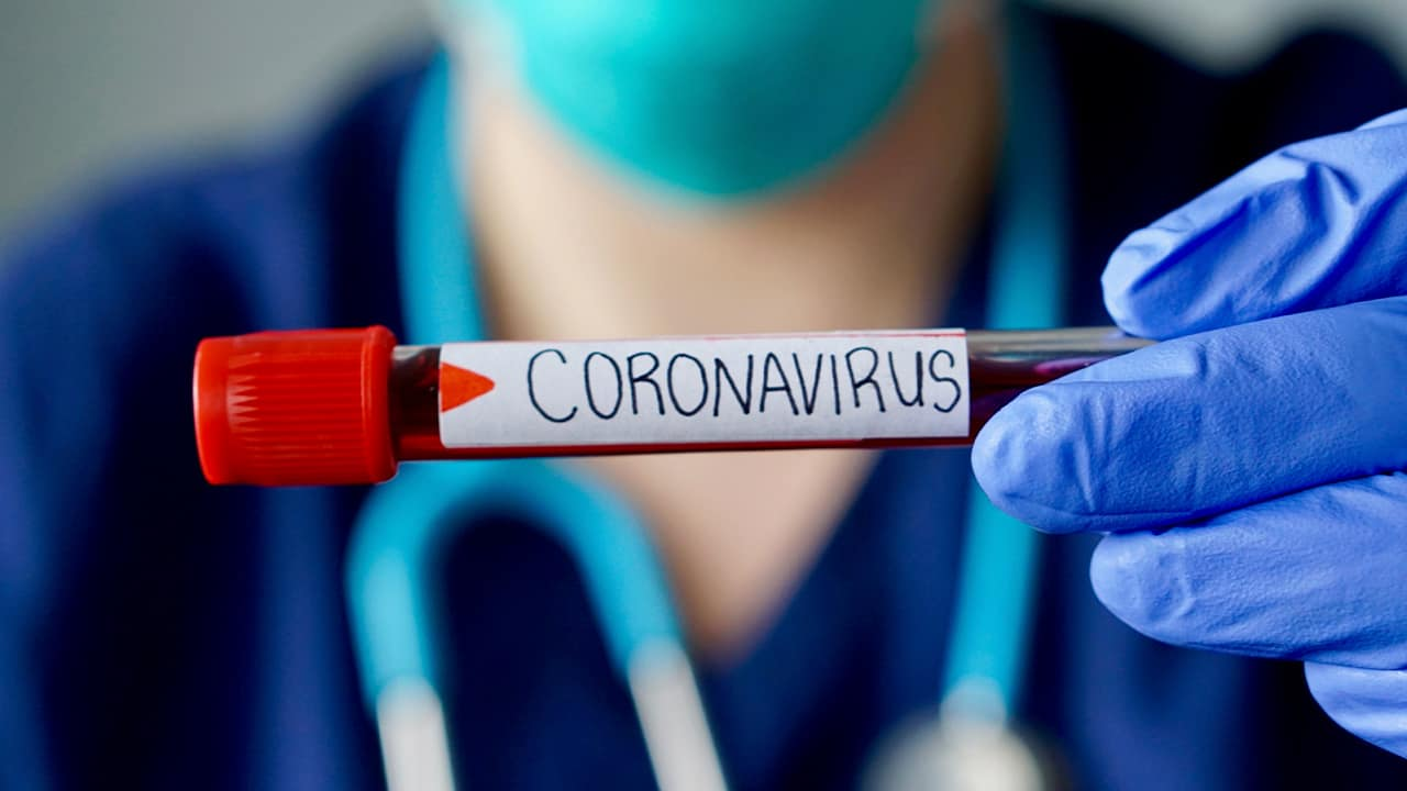 Photo of a physician holding a vial of blood marked coronavirus