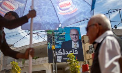 Photo of Israeli Arabs in a coffee shop near an election campaign poster showing Israeli Politician Ahmad Tibi of the Joint List in Tira, Israel