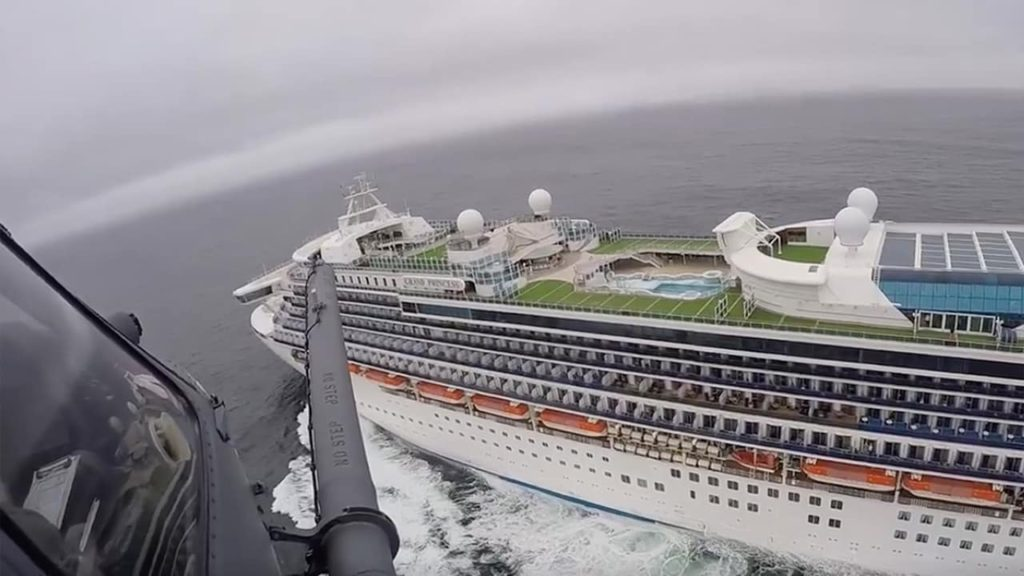 Photo of a helicopter carrying airmen with the 129th Rescue Wing flying over the Grand Princess cruise ship