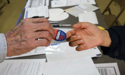 """Photo of someone being handed an """"I Voted"""" sticker"""