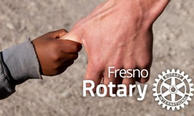 Composite of a man grabbing a child's hand with the Fresno Rotary logo po