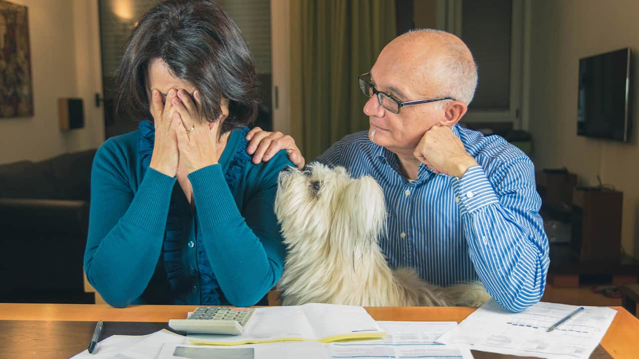 A worried wife and husband with pet dog sitting at a table with piles of billsman