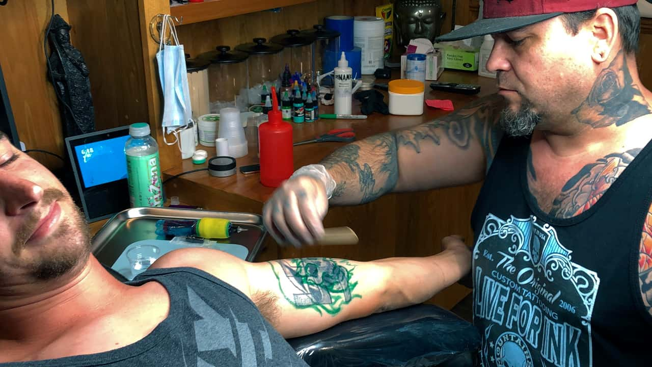Photo of a man getting a tattoo covered up