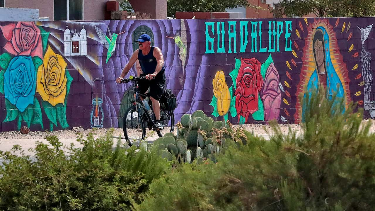 Photo of a man cycling past a mural