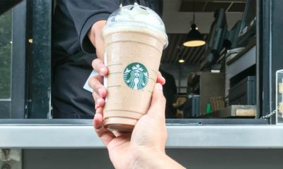 Image of a Starbucks employee handing a frappe mocha latte to a customer at drive thru counter.
