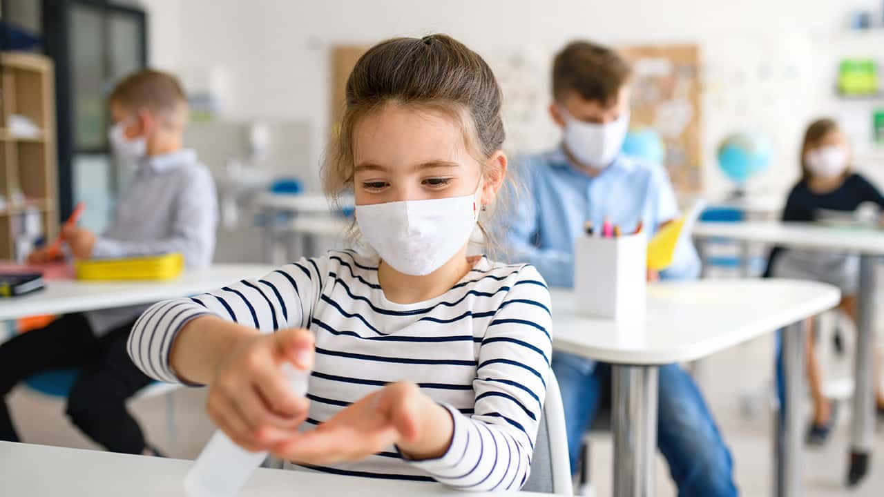 Image of a young student in a mask sanitizing her hands amid the coronavirus pandemic