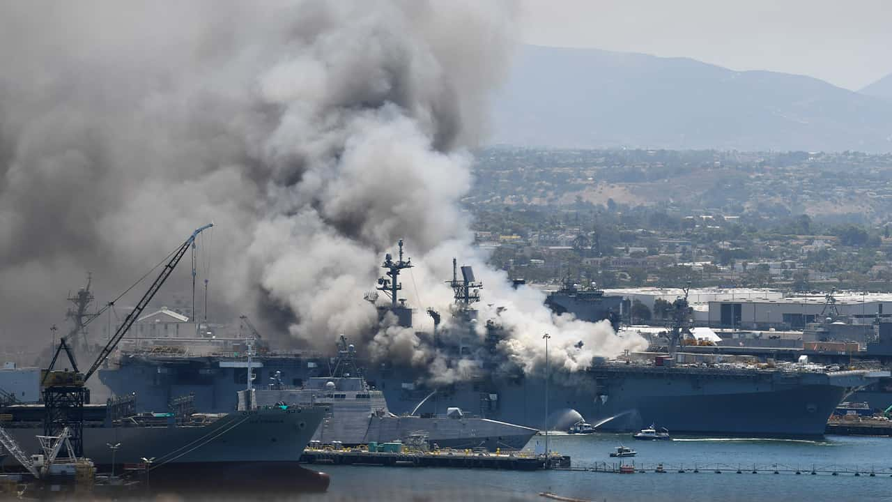Photo of smoke rising from the USS Bonhomme Richard at Naval Base San Diego