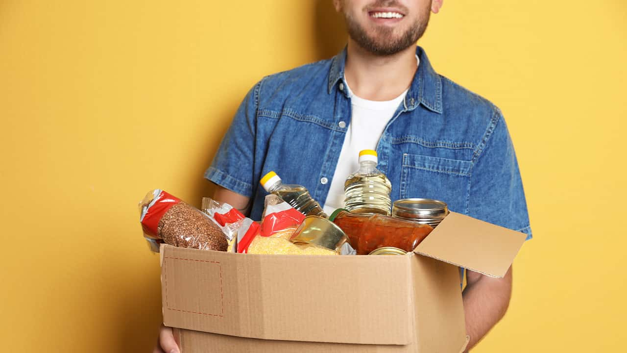 Picture of a young man carrying a box of donated groceries