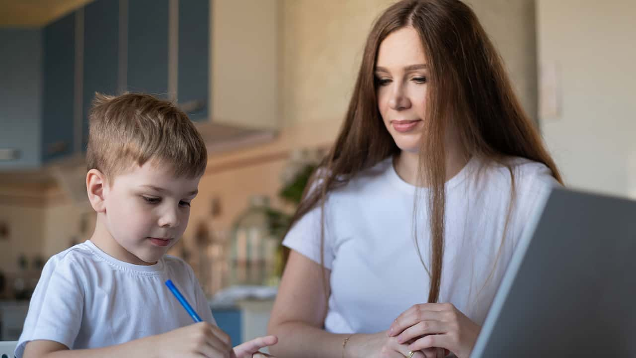 Photo of a caring mom helping her son with distance learning during the pandemic