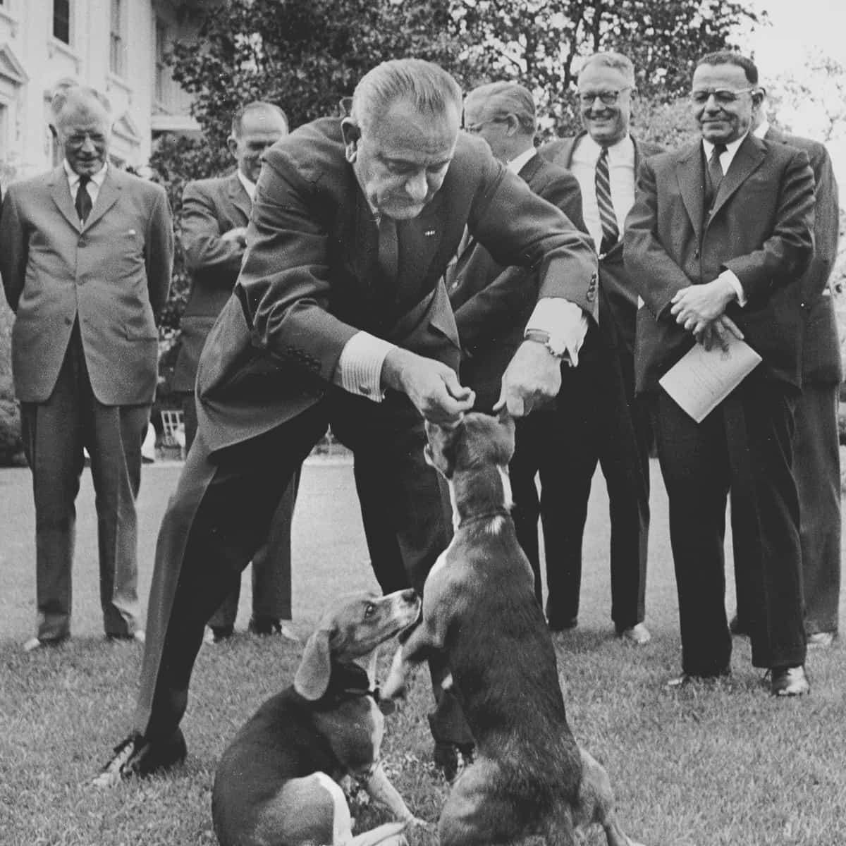 """FILE – In this April 27, 1964, file photo President Lyndon B. Johnson holds his dog """"Her"""" by the ears as White House visitors look on the White House lawn, Washington. At left is President Johnson's other dog, """"Him."""" This picture raised criticism from dog lovers. (AP Photo/Charles P. Gorry, File)"""