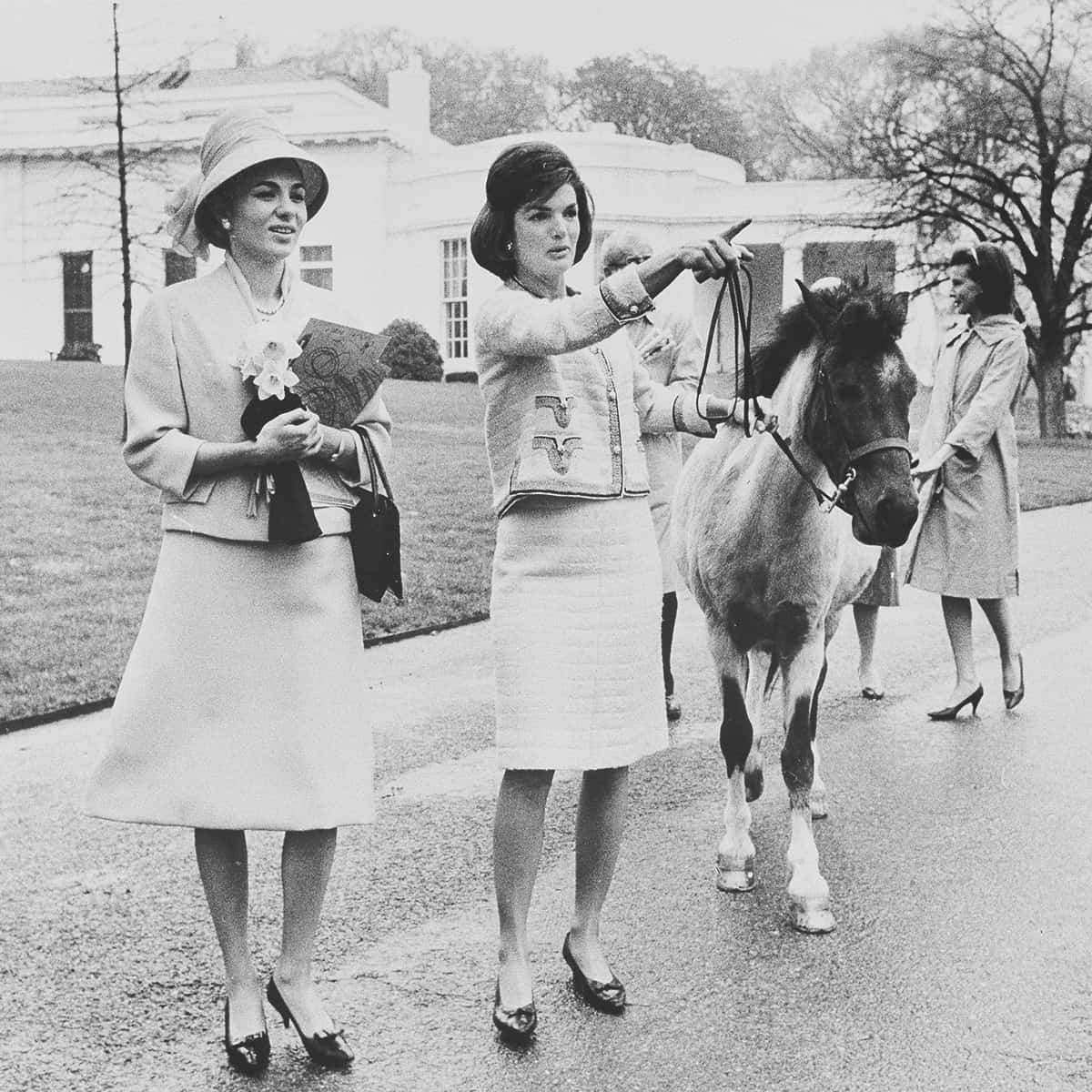 FILE – In this April 12, 1962, file photo first lady Jacqueline Kennedy gives a guided tour of the White House grounds to Empress Farah Pahlavi of Iran in Washington. Kennedy leads her daughter Caroline's pony, Macaroni, which had been nuzzling the empress, attracted by the daffodils she was carrying. In the background is the first lady's press secretary, Pamela Turnure. (AP Photo/Pool, File)
