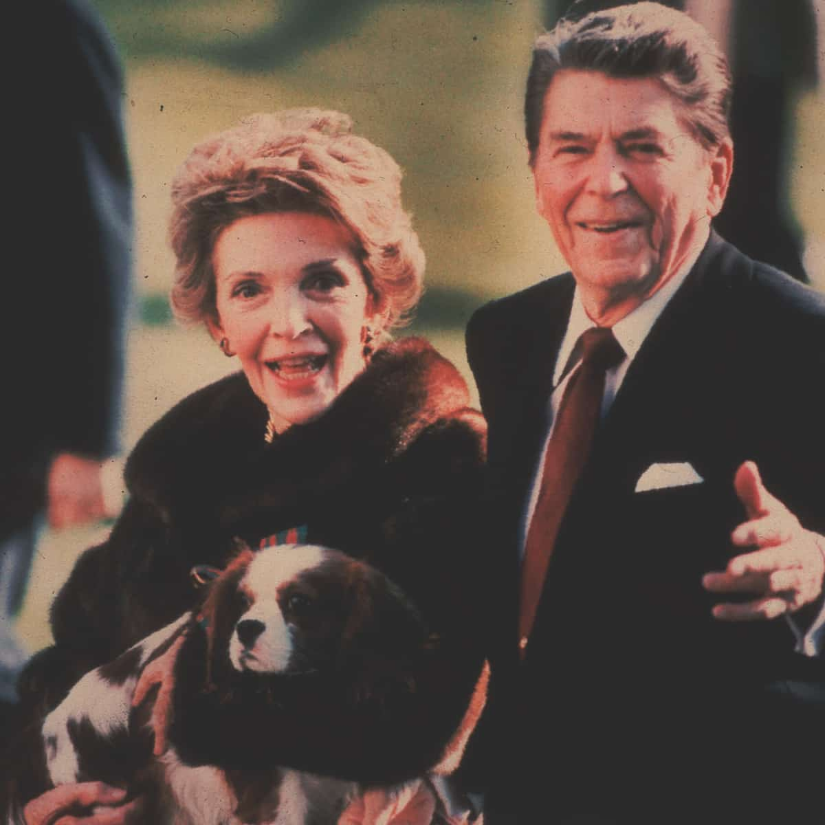 FILE – This December 1986, file photo shows first lady Nancy Reagan holding the Reagans' pet Rex, a King Charles spaniel, as she and President Reagan walk on the White House South lawn. (AP Photo/Dennis Cook, File)